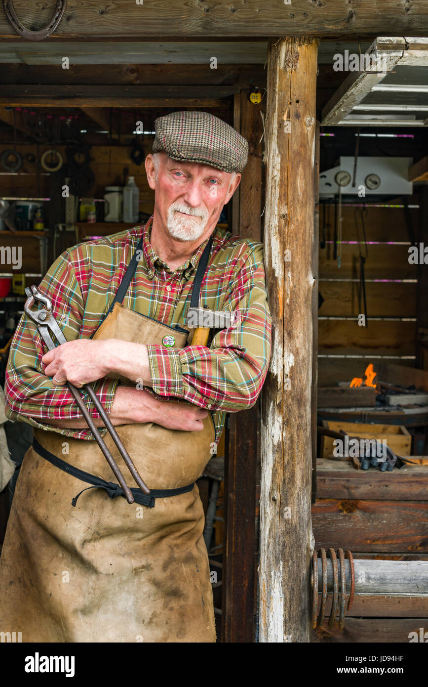 Male Blacksmith Standing Outside Small Forge Workshop Holding Tongs And Hammer - Stock Image