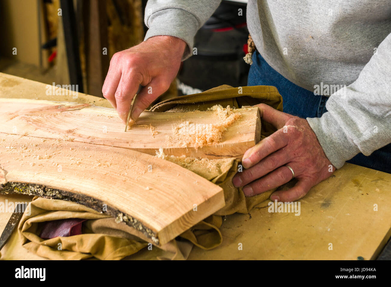 Woodworker Smoothing Wood With Glass In Workshop - Stock Image
