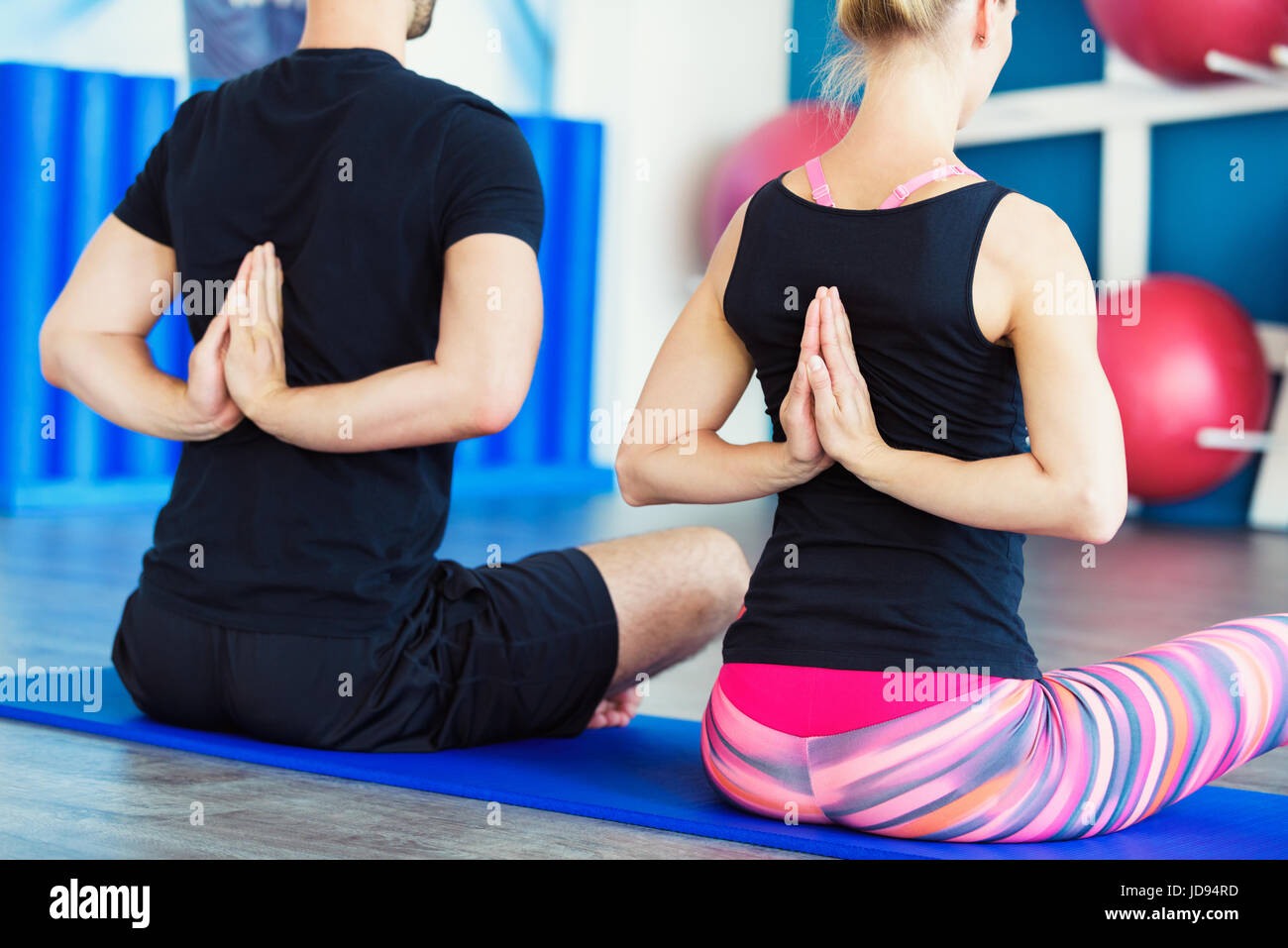 Nice couple doing yoga in a studio. Young people in yoga class in Reverse Prayer Pose. Yoga group concept - Stock Image