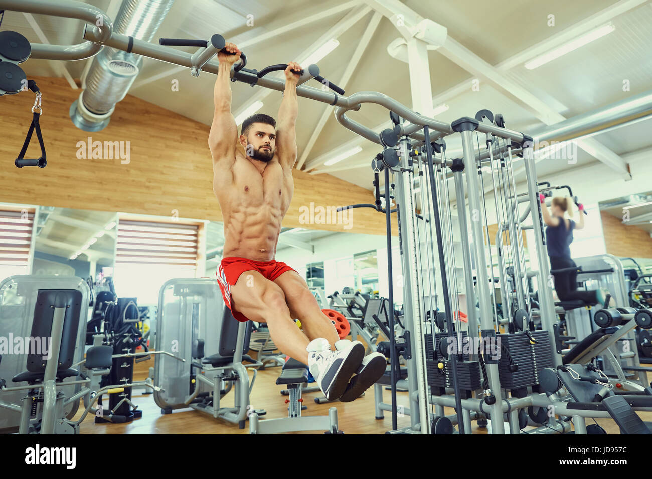 A man doing abs workouts on pull up bar in gym - Stock Image