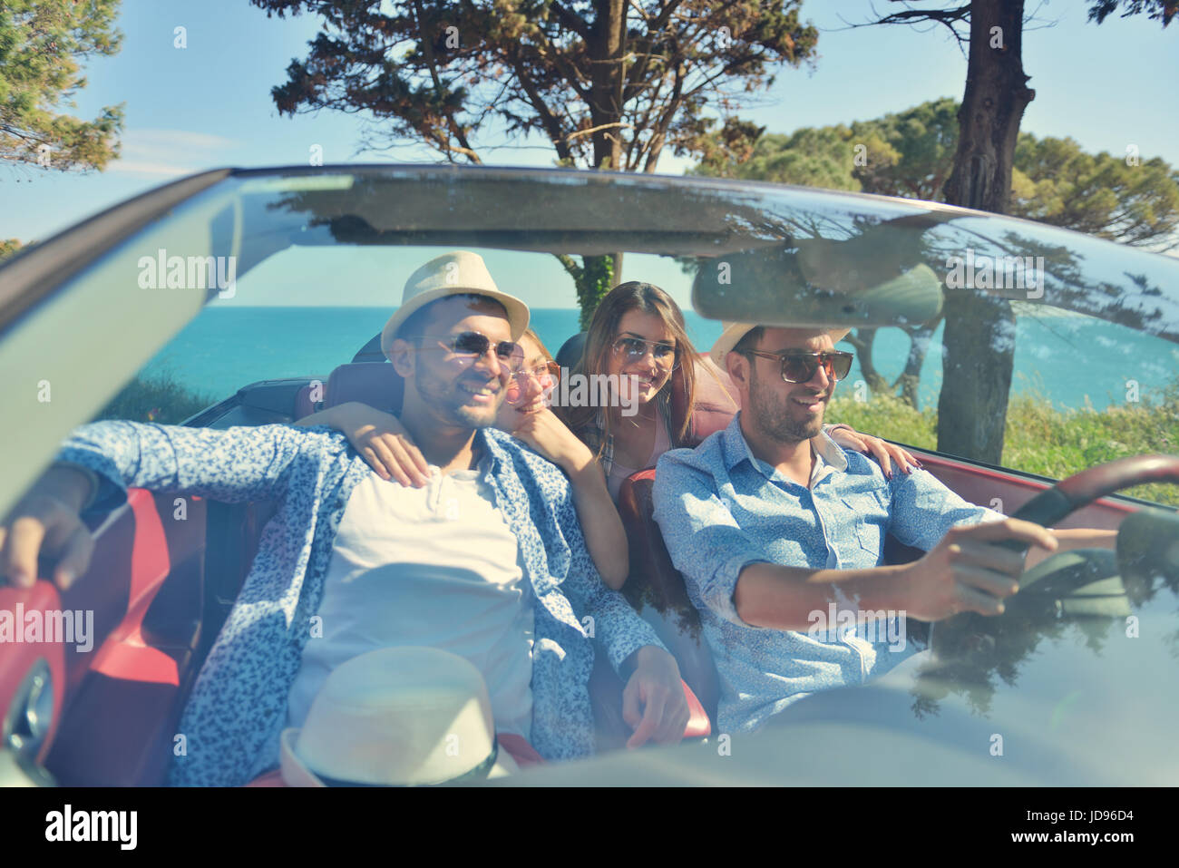 leisure, road trip, travel and people concept - happy friends driving in cabriolet car along country road - Stock Image