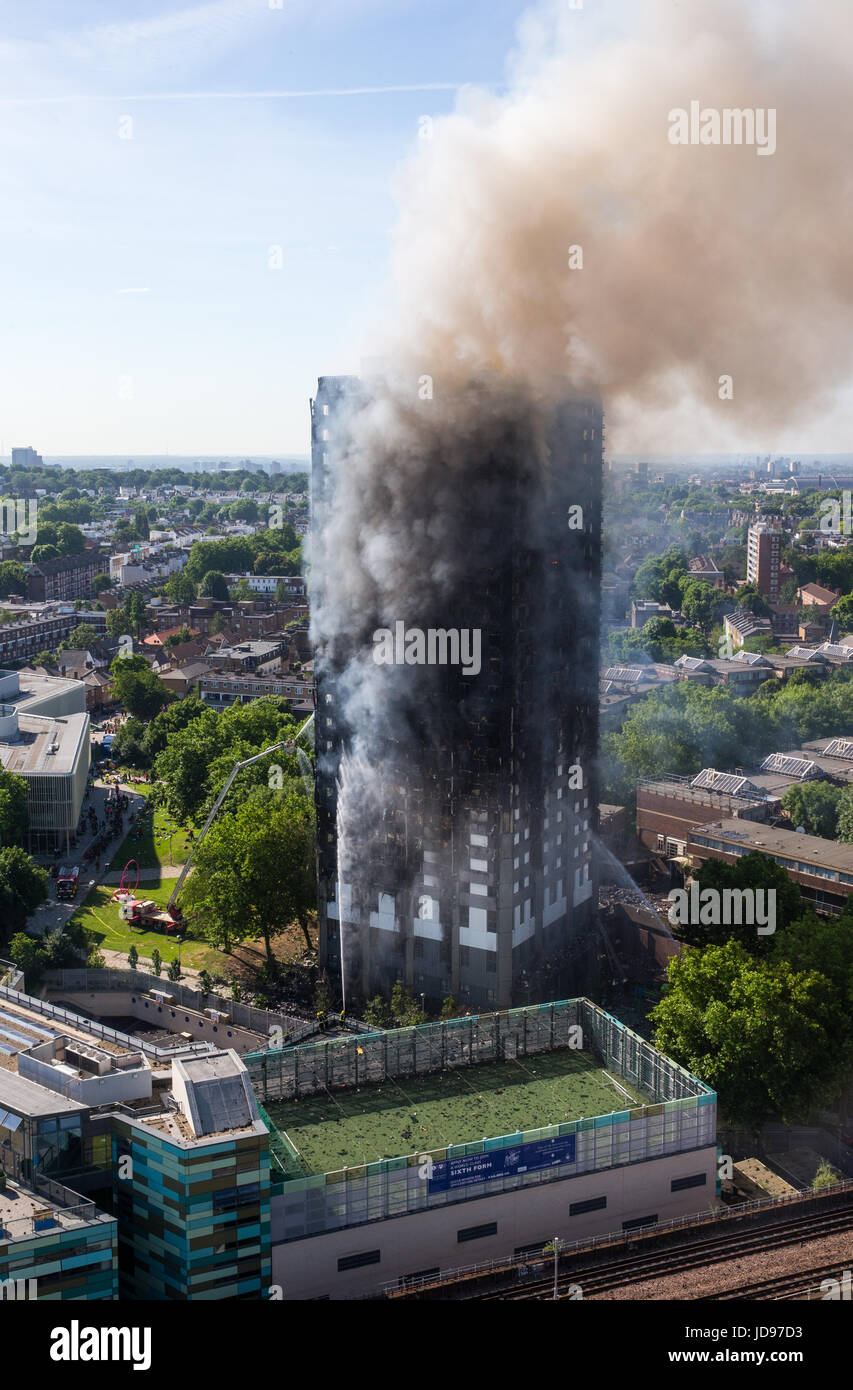 Fire burns at Grenfell Tower in Latimer road, London.The fire stared on the 4th floor when a fridge caught fire. - Stock Image
