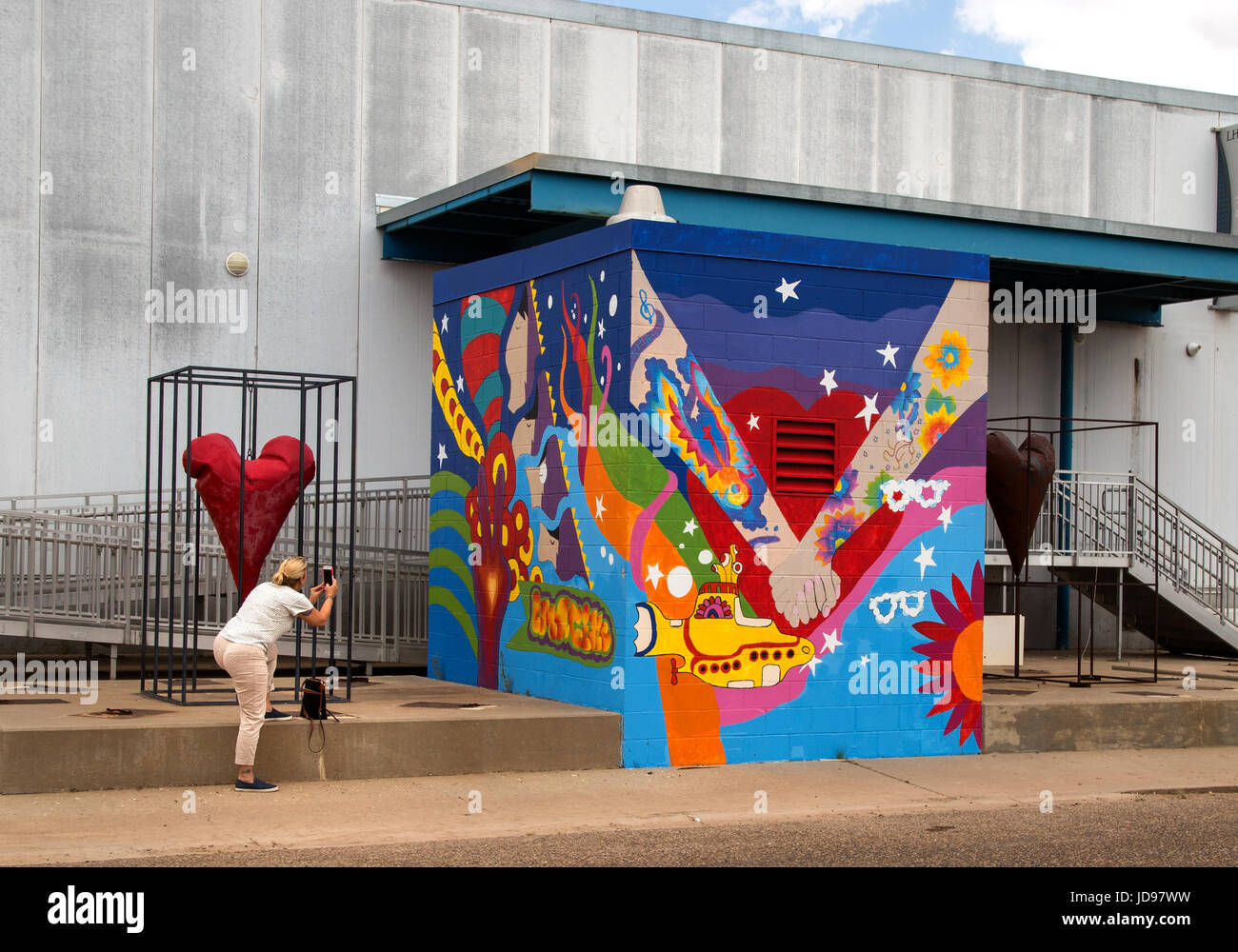 Woman taking photos of street art in the Depot District of Lubbock Texas - Stock Image