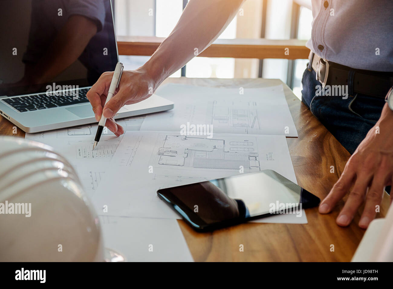 Architects engineer discussing at the table with blueprint - Closeup on hands and project print. - Stock Image