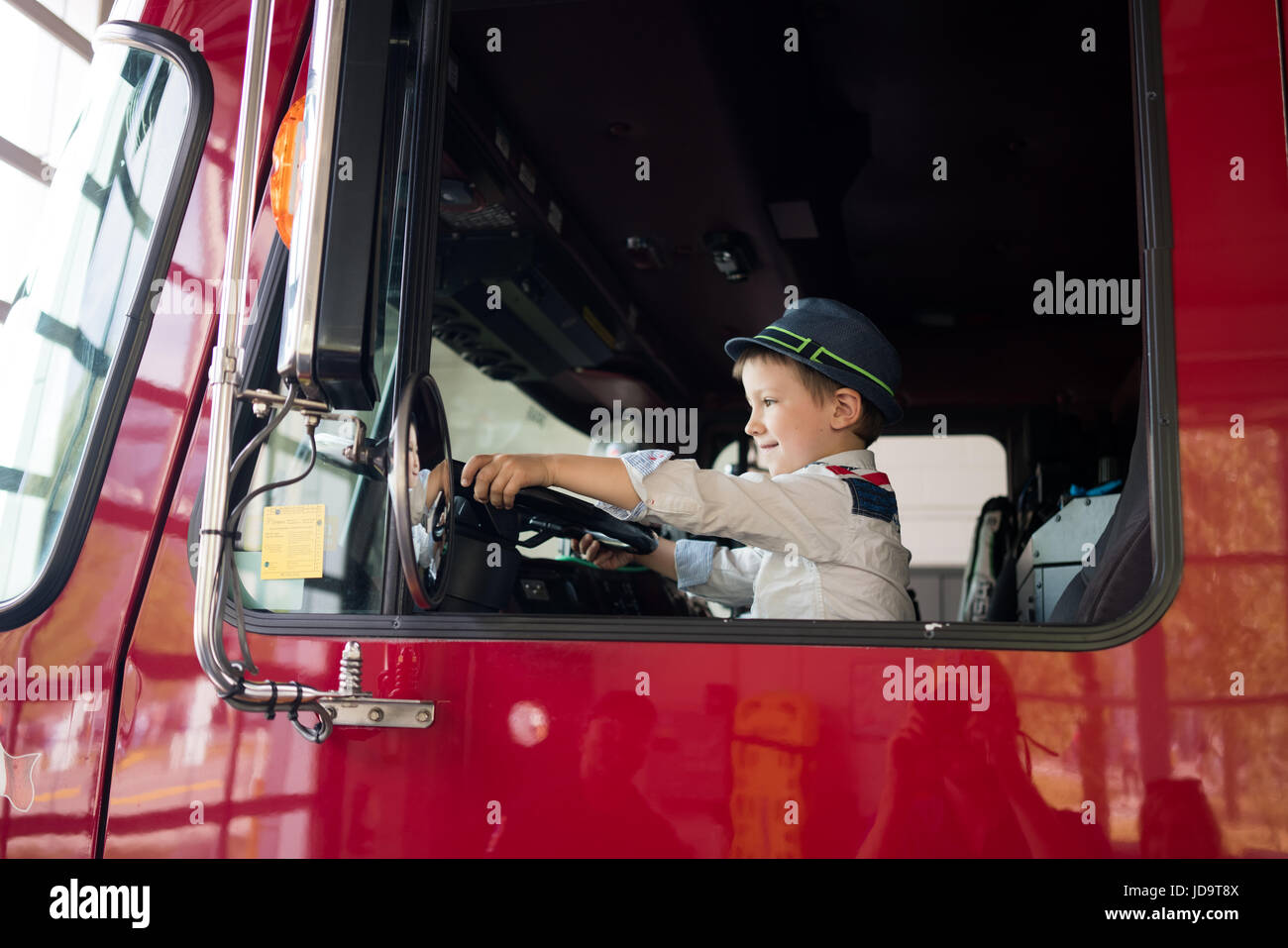 Young boy in driving seat of truck, holding steering wheel, smiling - Stock Image