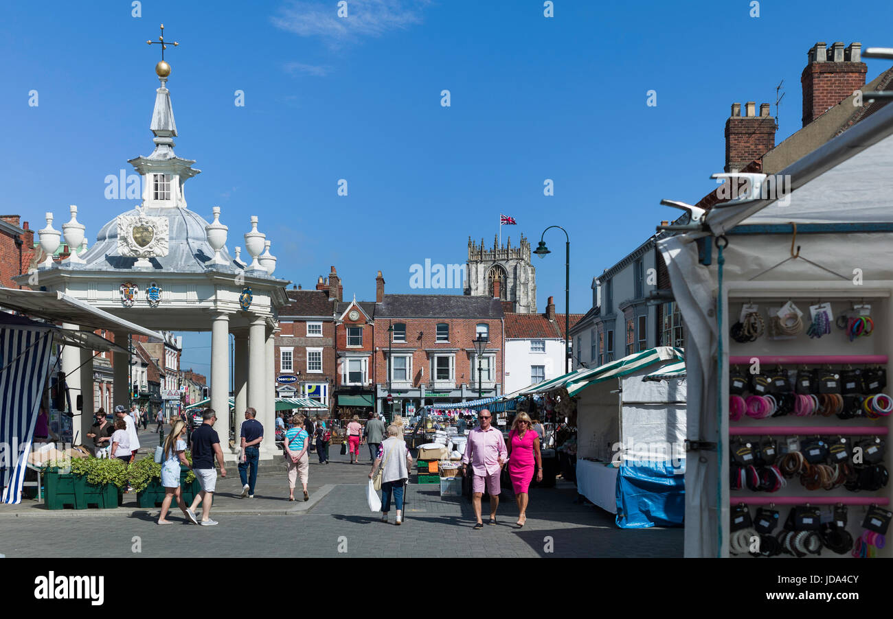 Shoppers enjoy the popular Saturday Market with view of the bandstand and St Mary's Church on a sunny morning - Stock Image