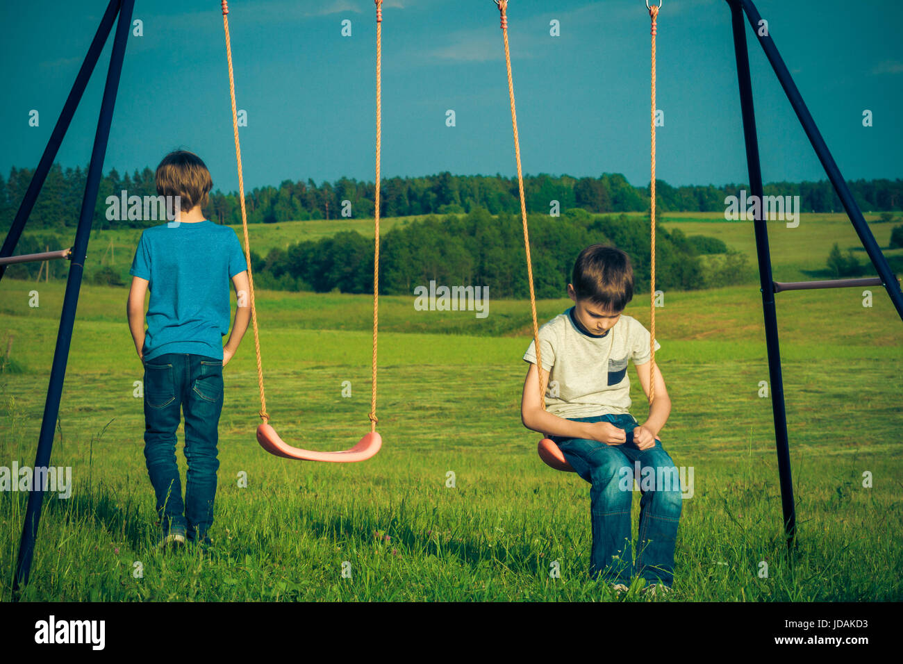Kids relationship difficulties. Child falls out with a friend outdoors - Stock Image