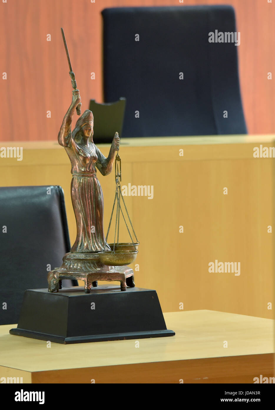 A law statue in front of court bench - Stock Image