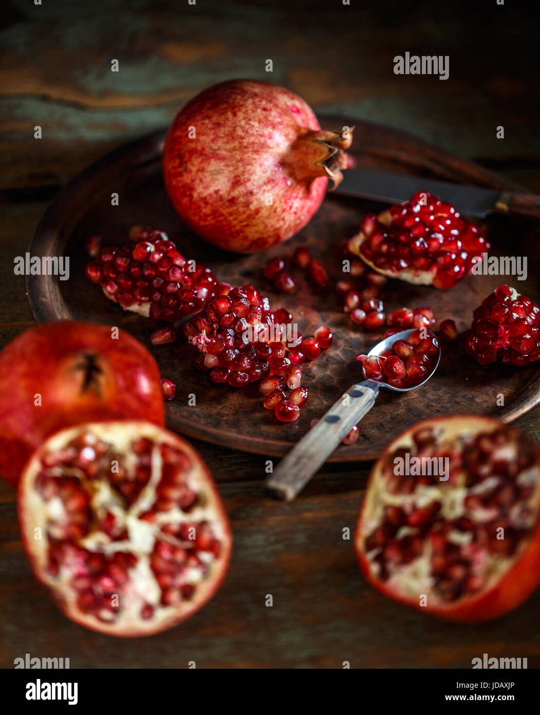 Broken and whole red ripe juicy pomegranates - Stock Image
