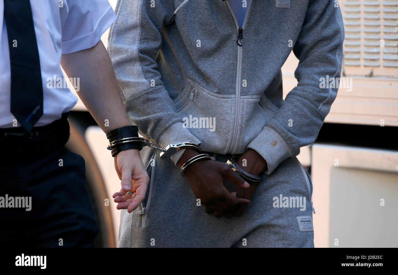 A Geoamey custody officer leads a prisoner into Lewes Crown Court in handcuffs. June 19, 2017. James Boardman / - Stock Image