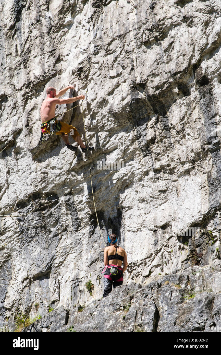 Male and female rock climbers climbing on limestone rockface at Malham Cove. Malham Malhamdale Yorkshire Dales National - Stock Image