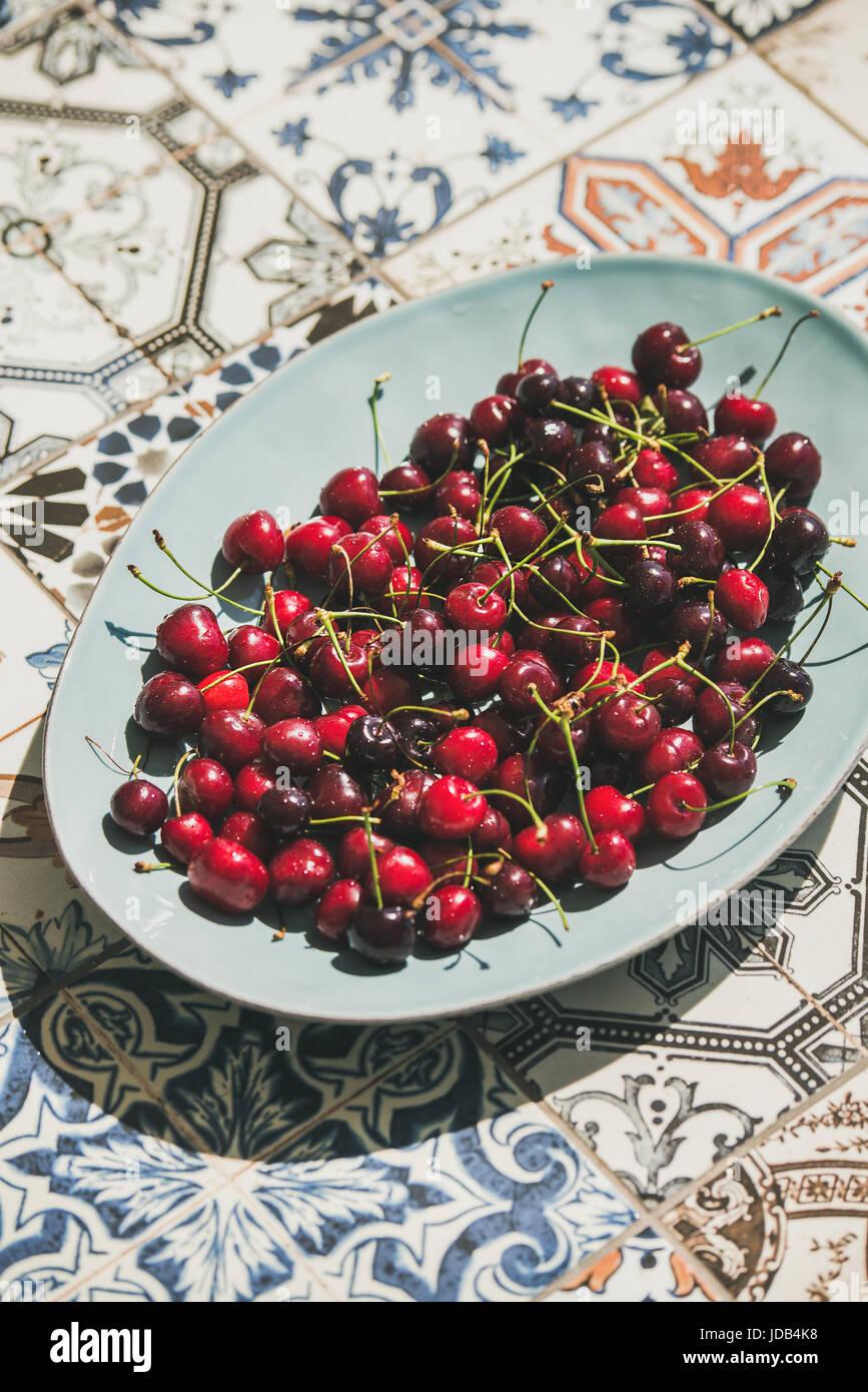 Fresh sweet cherries over oriental ceramic tiles background - Stock Image
