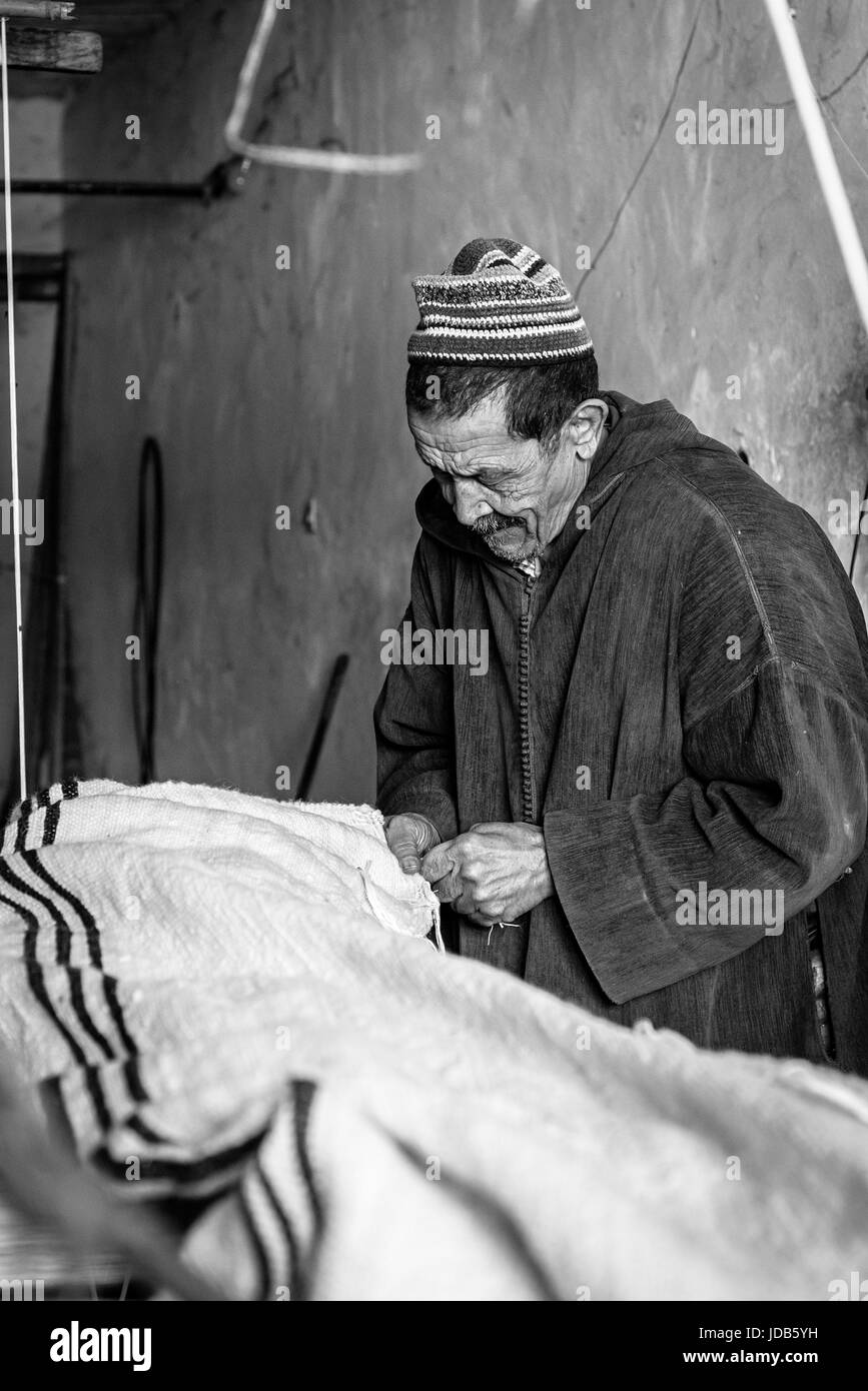 Old man working on a loom in a small village in Essaouira - Stock Image