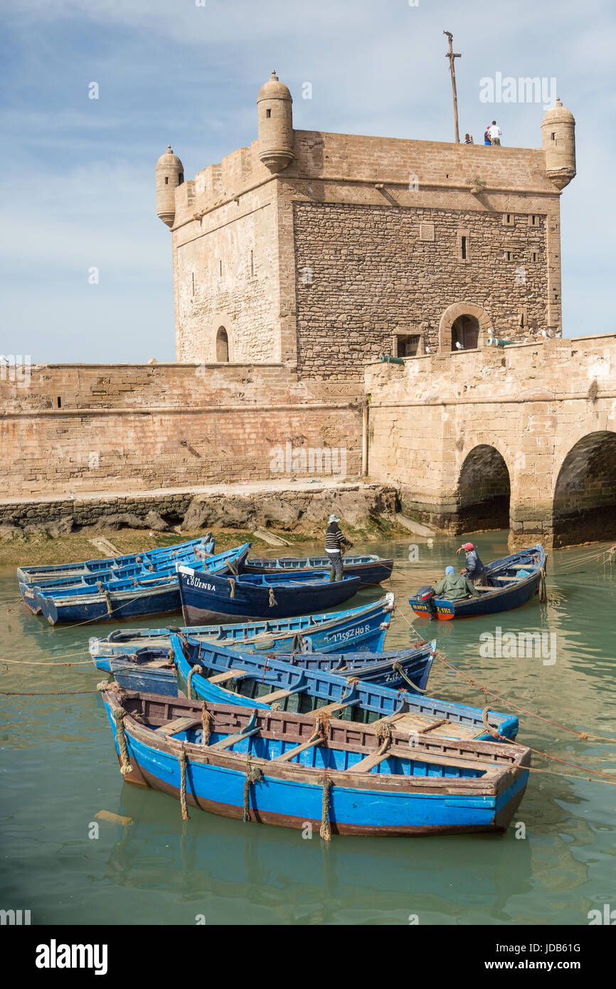 Blue painted boats belonging to fisherman lie inside the old harbour of Essaouira, Morocco Stock Photo