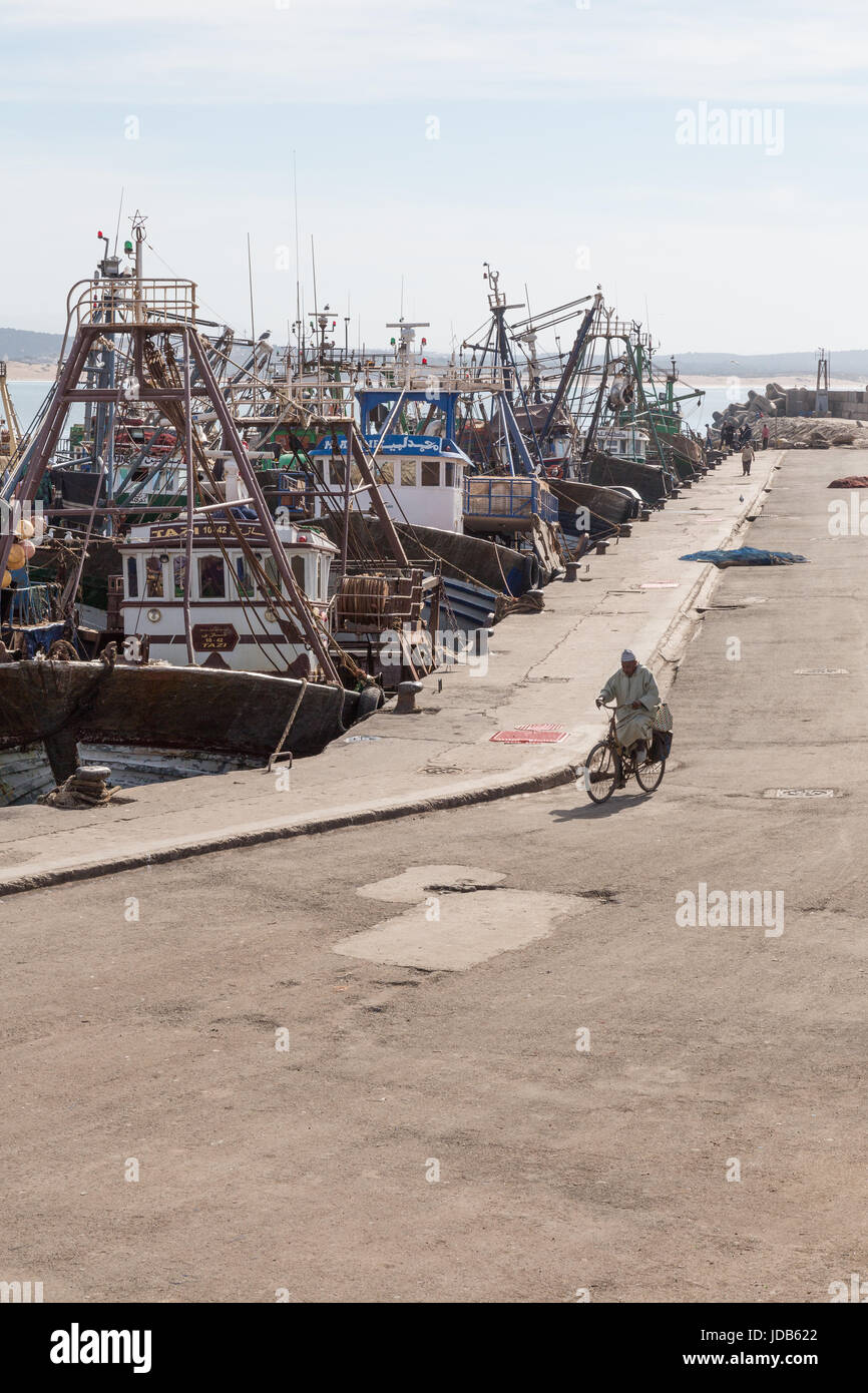 A man cycles down the quiet docks of the new port in Essaouira, Morocco Stock Photo