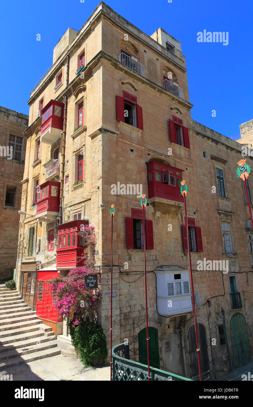 Red balconies and shutters historic building in city centre of Valletta, Malta - Stock Image