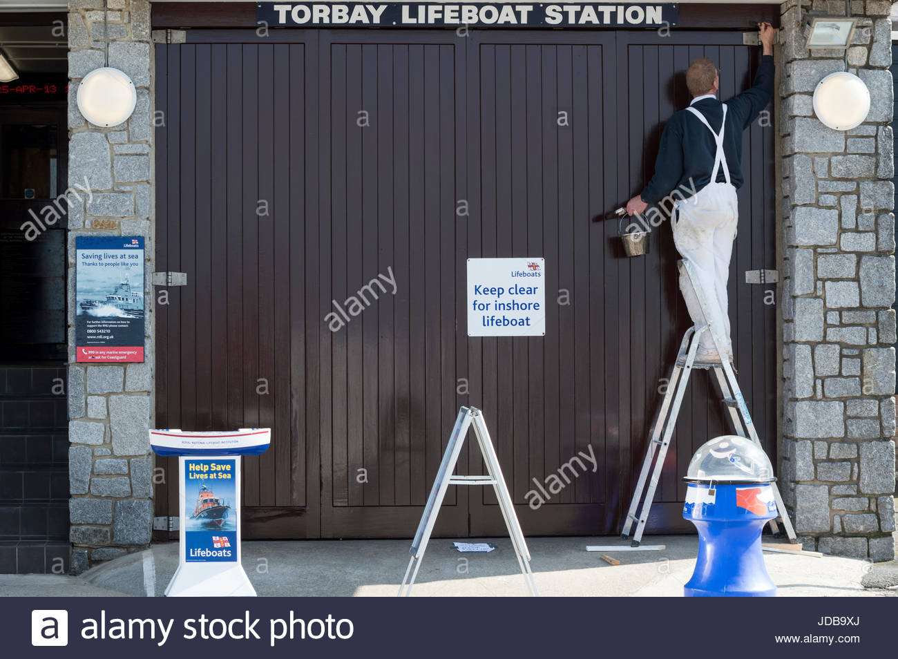 Workman up a ladder decorating the outside of the Torbay Lifeboat Station, Brixham, Devon, England - Stock Image