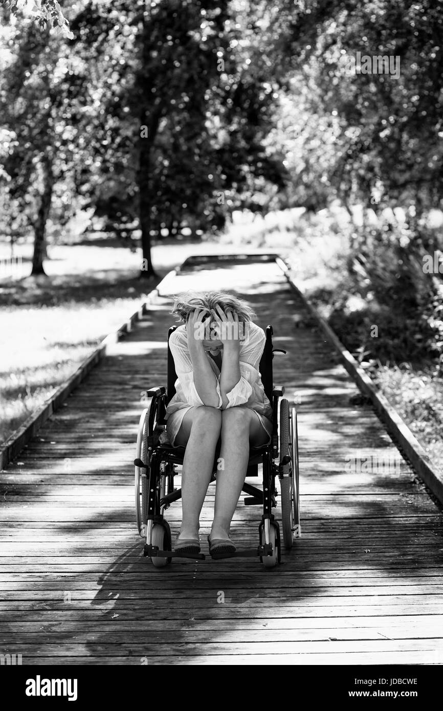 sad young adult woman on wheelchair in the park holding her head in surrender, black and white - Stock Image