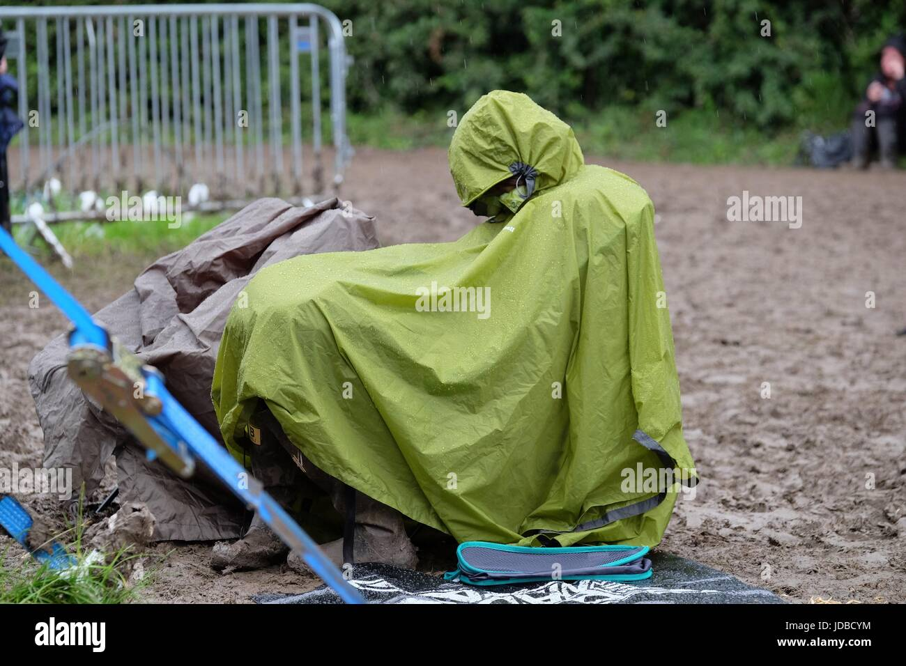 Festival goer sitting in a rain poncho and wellies at a muddy music festival - Stock Image