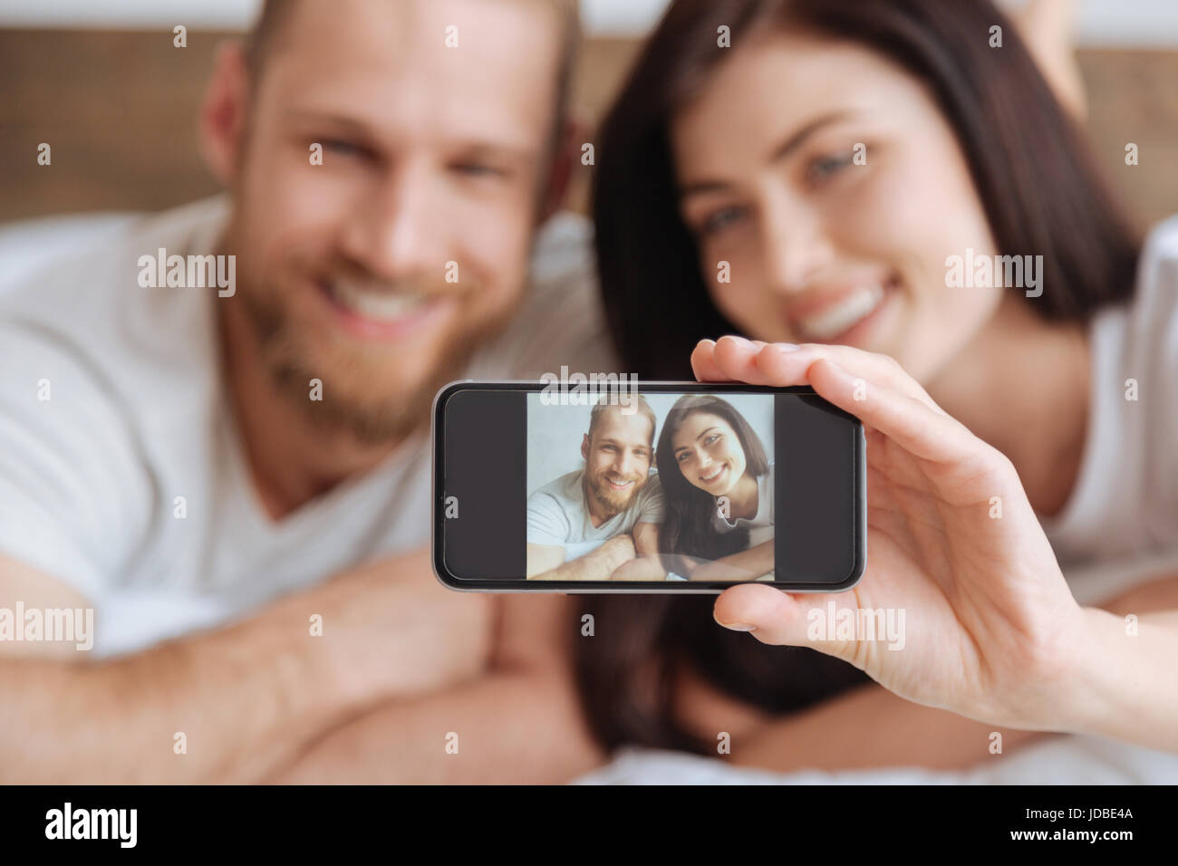 Young couple taking self portrait picture with smartphone - Stock Image