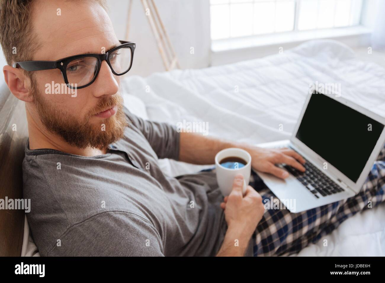 Bearded man sitting on bed with coffee and laptop - Stock Image