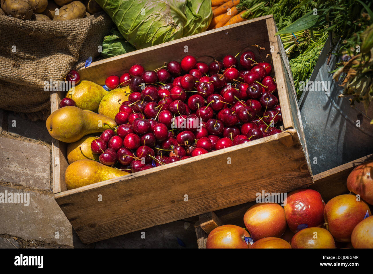 A display box of cherries and pears surrounded by various fruit and vegetables Stock Photo