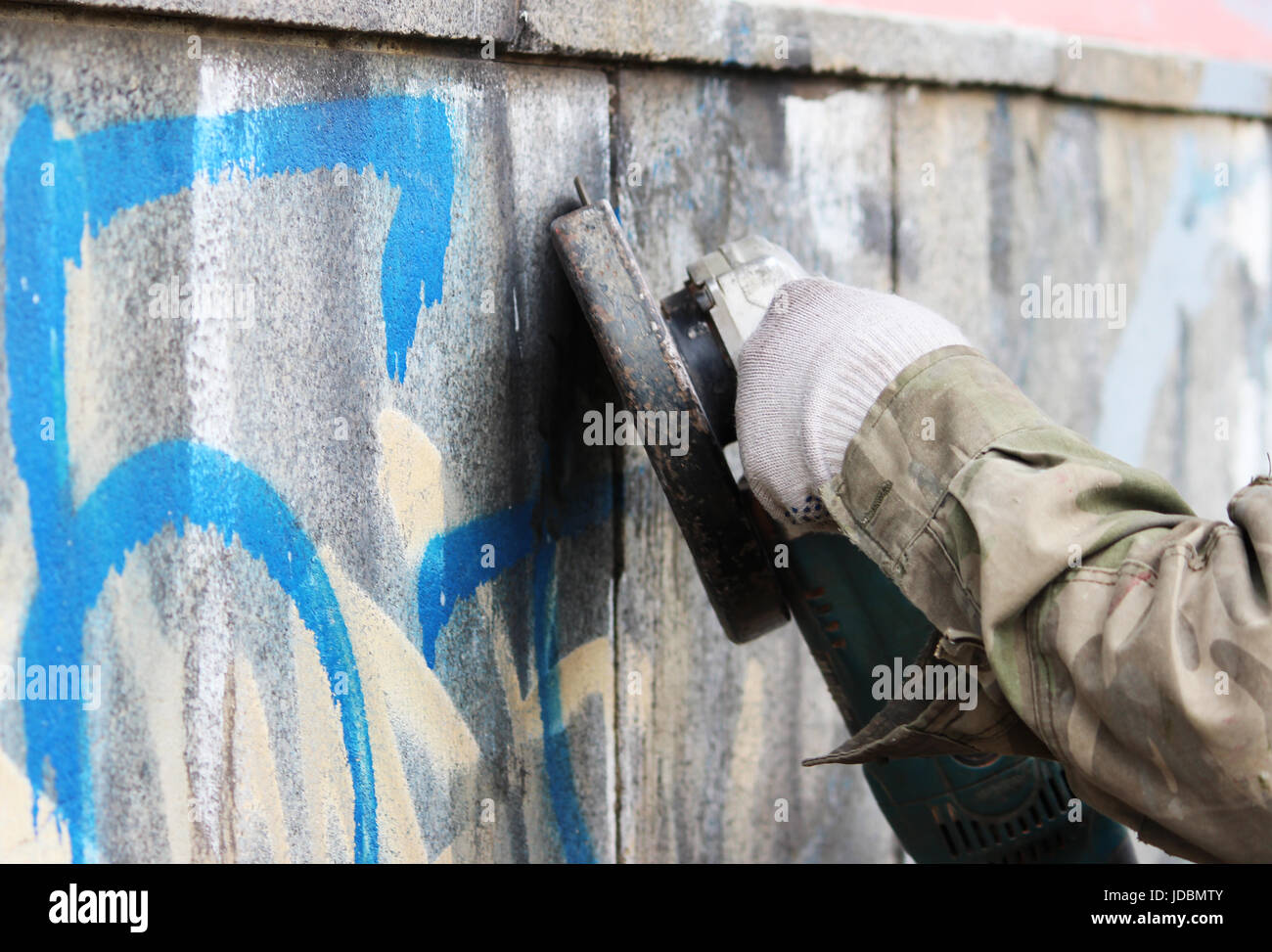 Removal of graffiti on a concrete wall of an underground passage with the help of a angle grinder - Stock Image