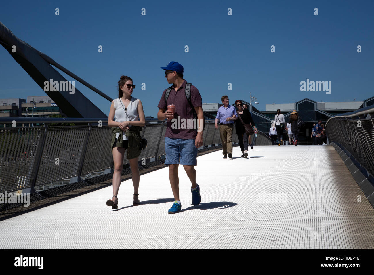 Tourists walking across a bridge in Dublin docklands, Ireland. - Stock Image