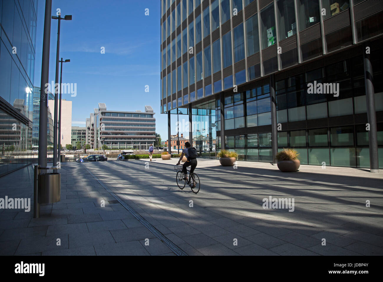 Cycling through Dublin docklands area, Ireland. - Stock Image