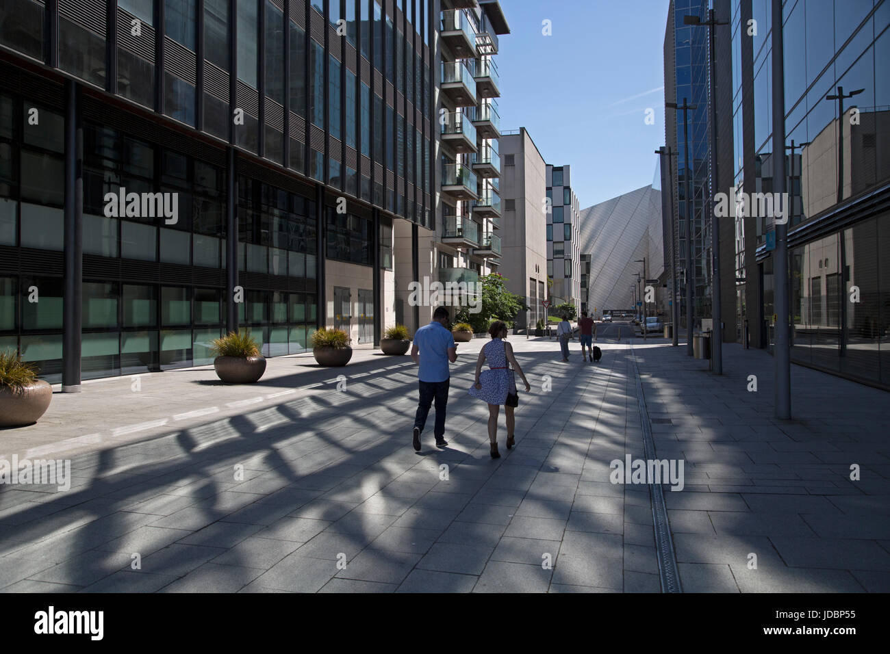 A couple walking in Dublin docklands. Ireland. - Stock Image