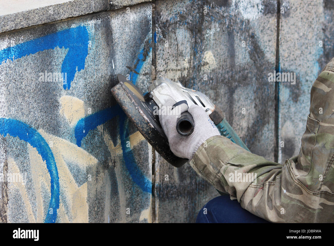 Removal of graffiti on a concrete wall of an underground passage ...