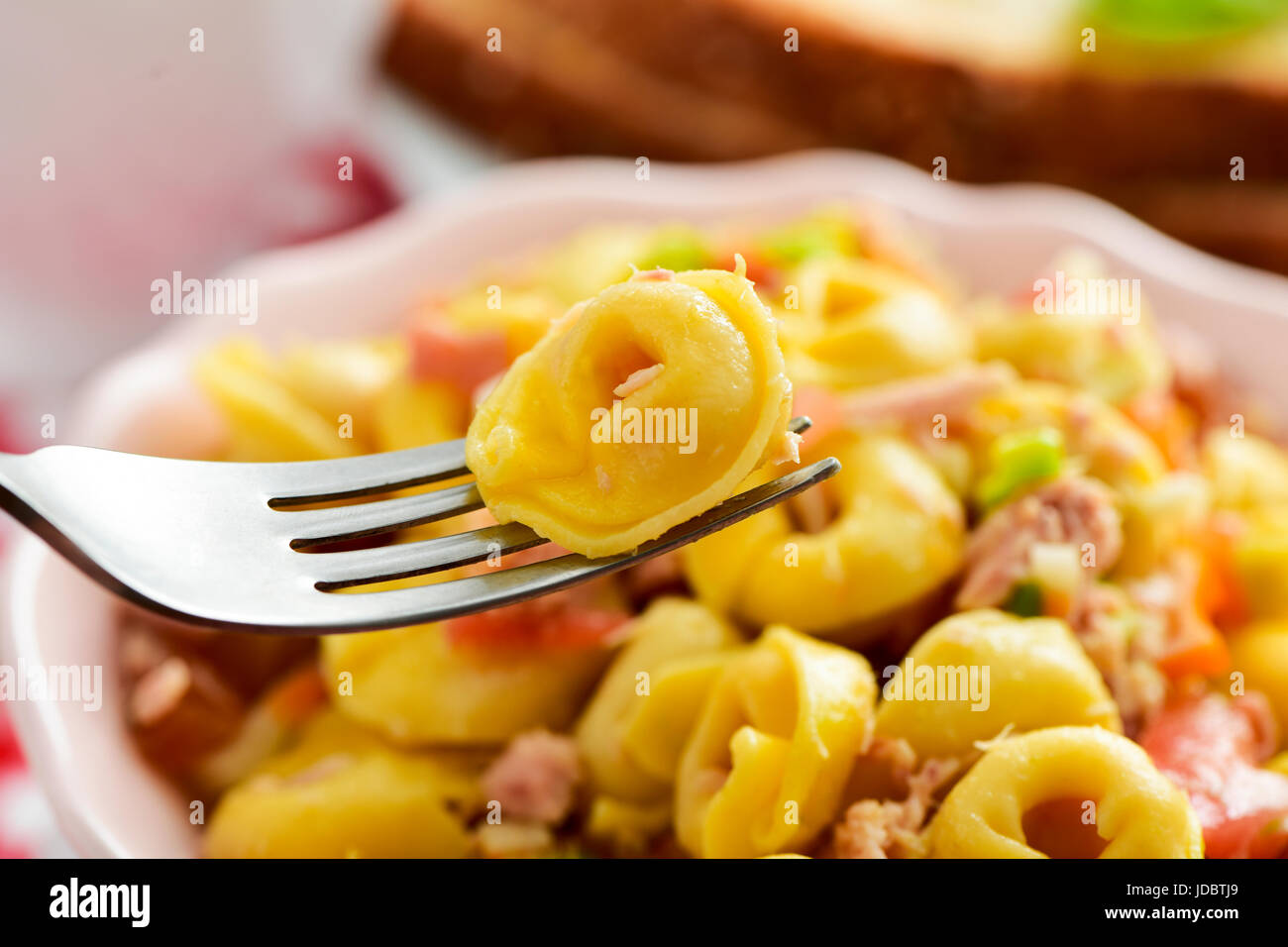 closeup of a ceramic bowl with a pasta salad made with tortellini on a table set for lunch or dinner - Stock Image