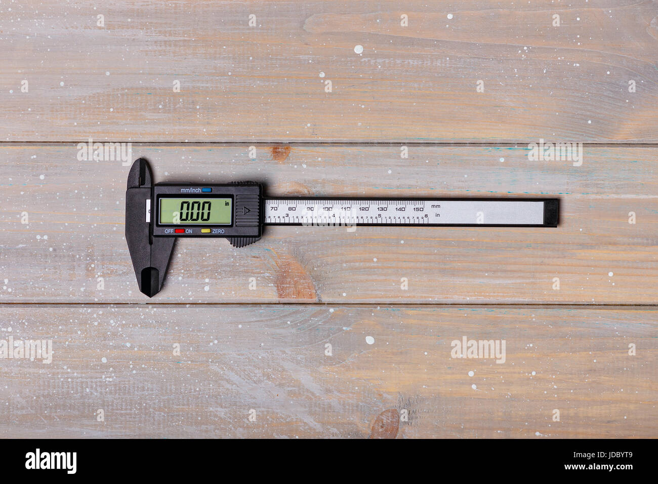 Closed digital caliper lies in the middle of a wooden table - Stock Image