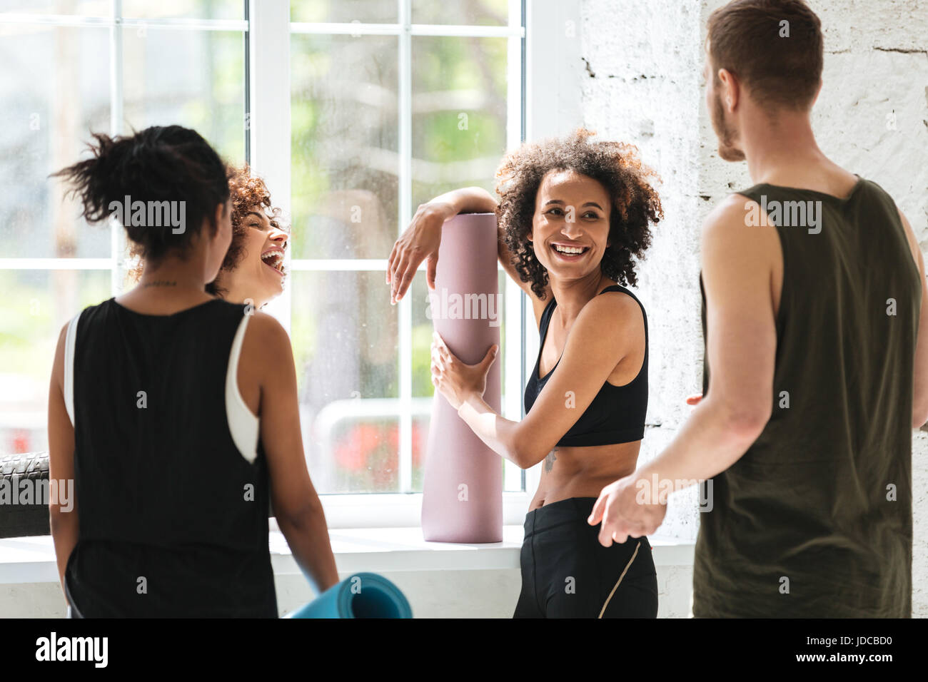 Smiling african woman talking with friends while doing yoga in gym Stock Photo