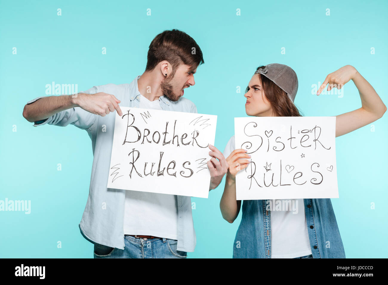 Young handsome brother and pretty sister holding funny nameplates over blue background. Looking aside. - Stock Image