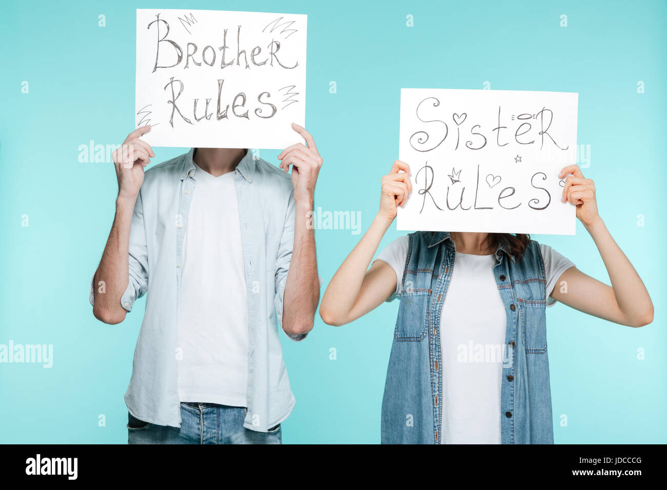 Picture of brother and sister holding funny nameplates over blue background. - Stock Image