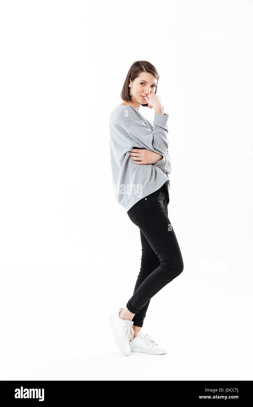 Full length side view portrait of a pensive young woman standing and looking at camera isolated over white background - Stock Image