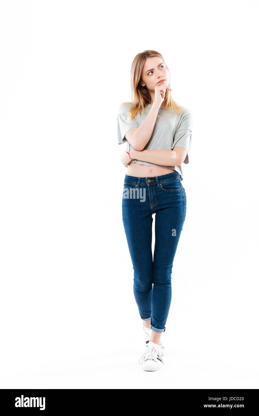 Full length portrait of a young thoughtful woman looking away isolated over white background - Stock Image