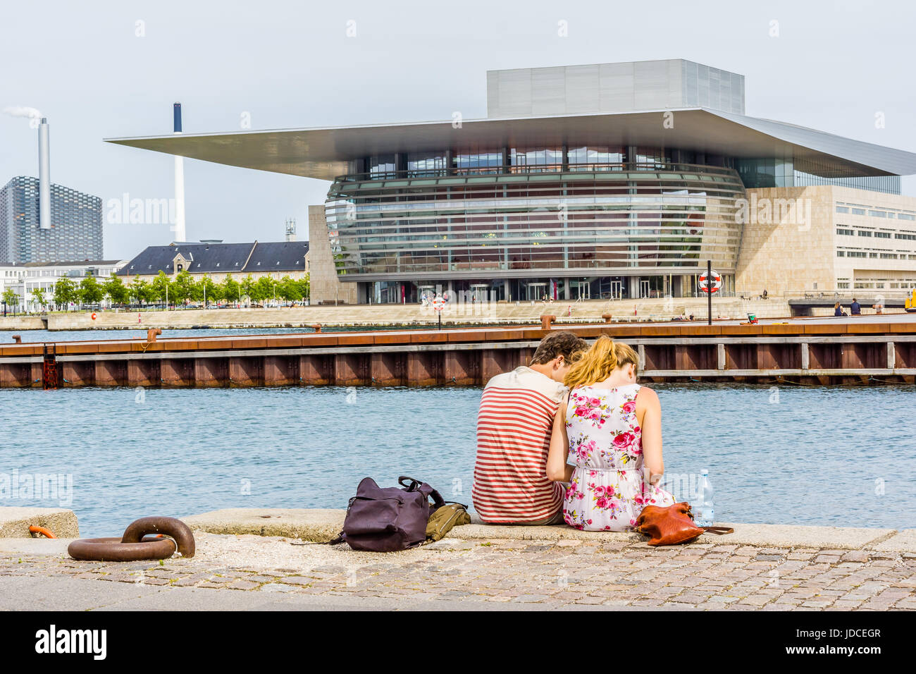Couple sitting on the  quayside in front of the Copenhagen Opera House on the island of Holmen in central Copenhagen. - Stock Image
