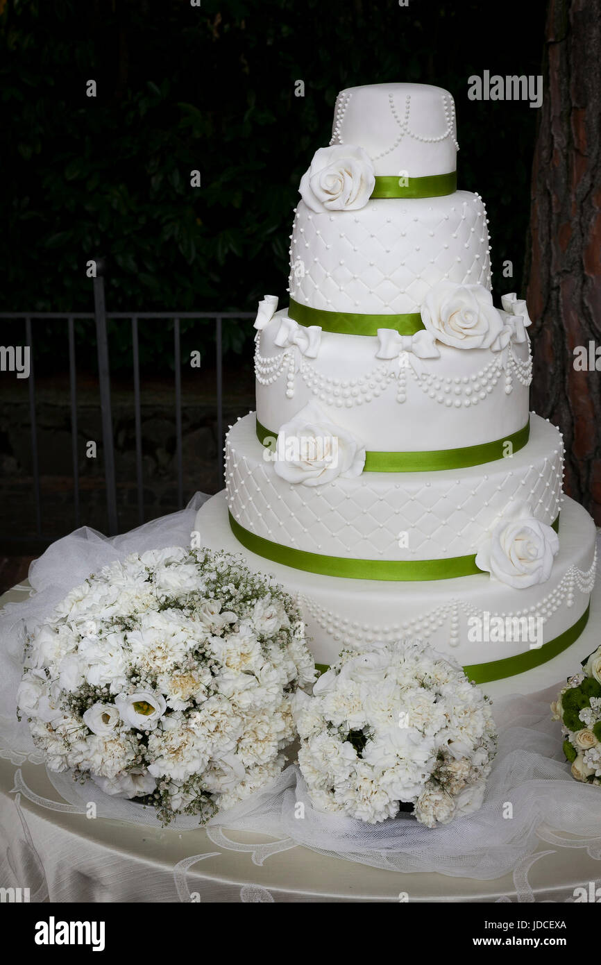 five-tiered white wedding cake covered with white roses and bouquet - Stock Image