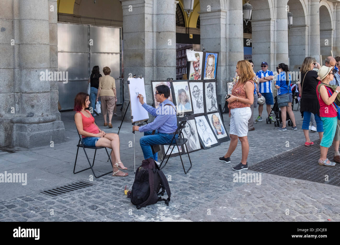 Street artist doing cartoon portrait caricatures for tourists, Plaza Major, Madrid, Spain - Stock Image
