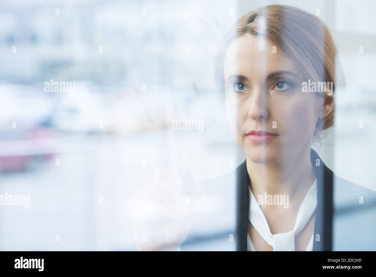 Portrait of pensive blonde businesswoman in formal wear looking through glass - Stock Image