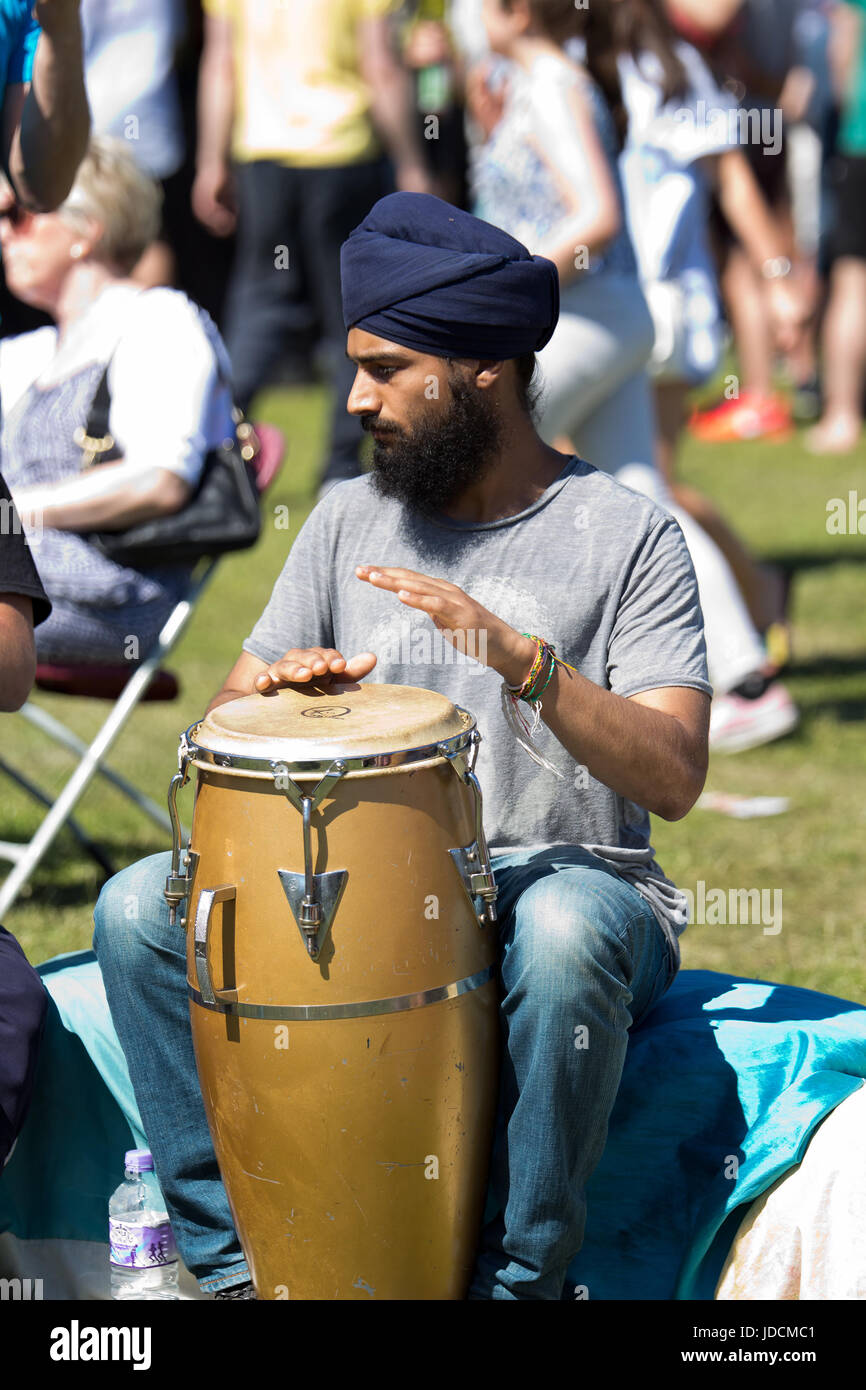 Young man wearing a turban learning to play African Drums at