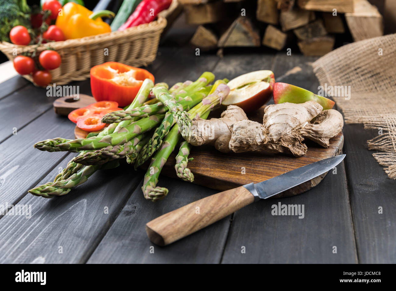 Close-up view of fresh seasonal vegetables and halved apple on wooden table top Stock Photo