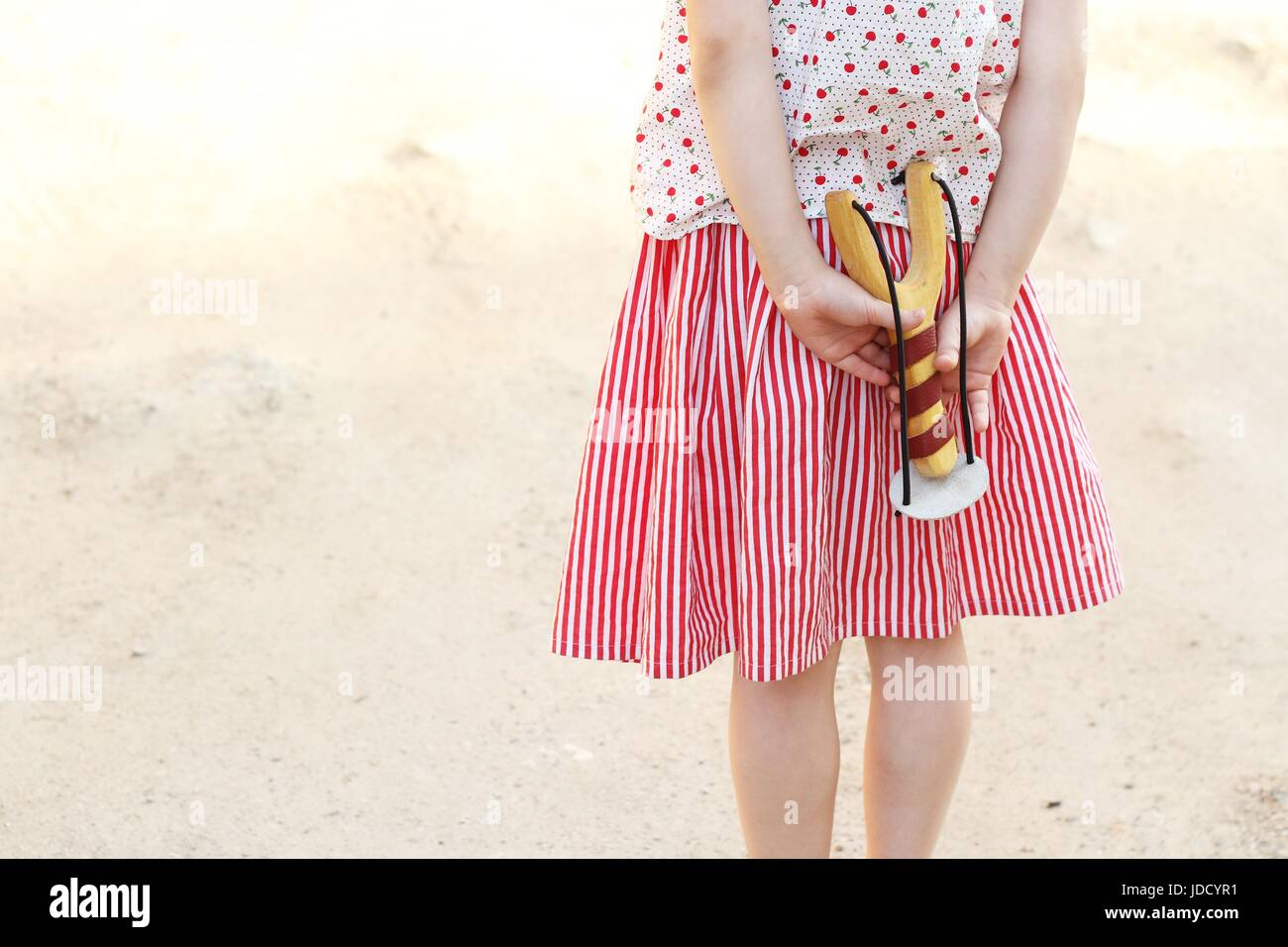 Girl holding a slingshot in her hands Girl holding a slingshot in her hands - Stock Image