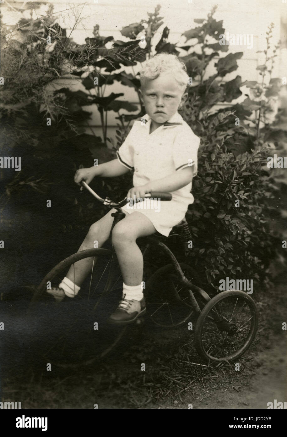Antique c1930 photograph, six year old boy on a tricycle. Location is probably Minnesota. SOURCE: ORIGINAL PHOTOGRAPH. - Stock Image