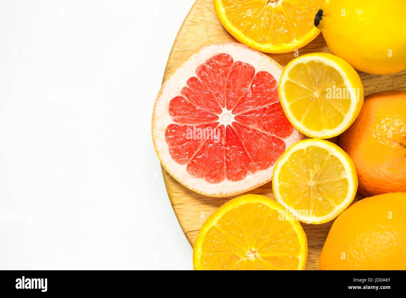 Vitamin C fruits - lemon, orange and grapefruits slices on woden cutting board on white background - Stock Image