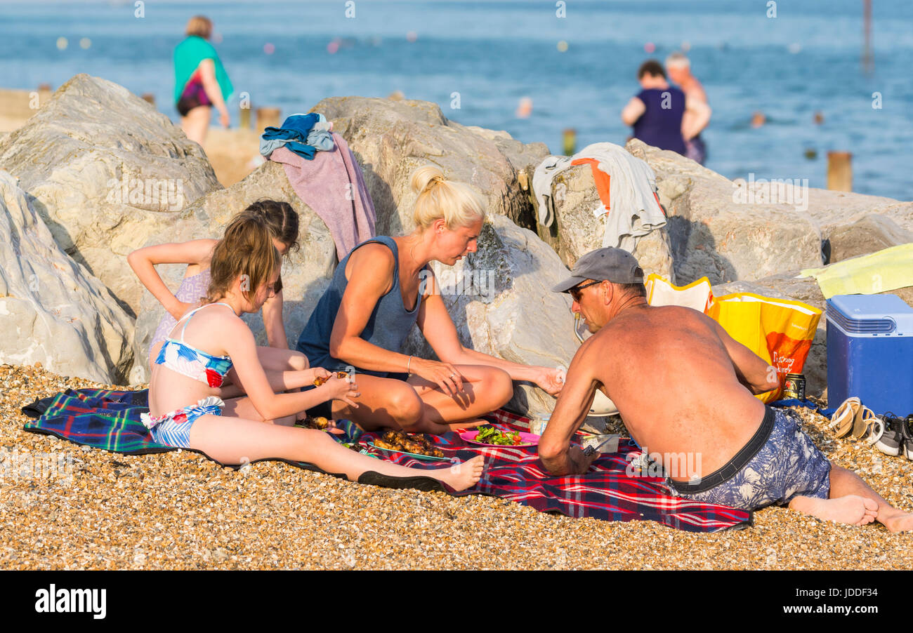 Family having their evening meal on the beach on a hot evening. - Stock Image