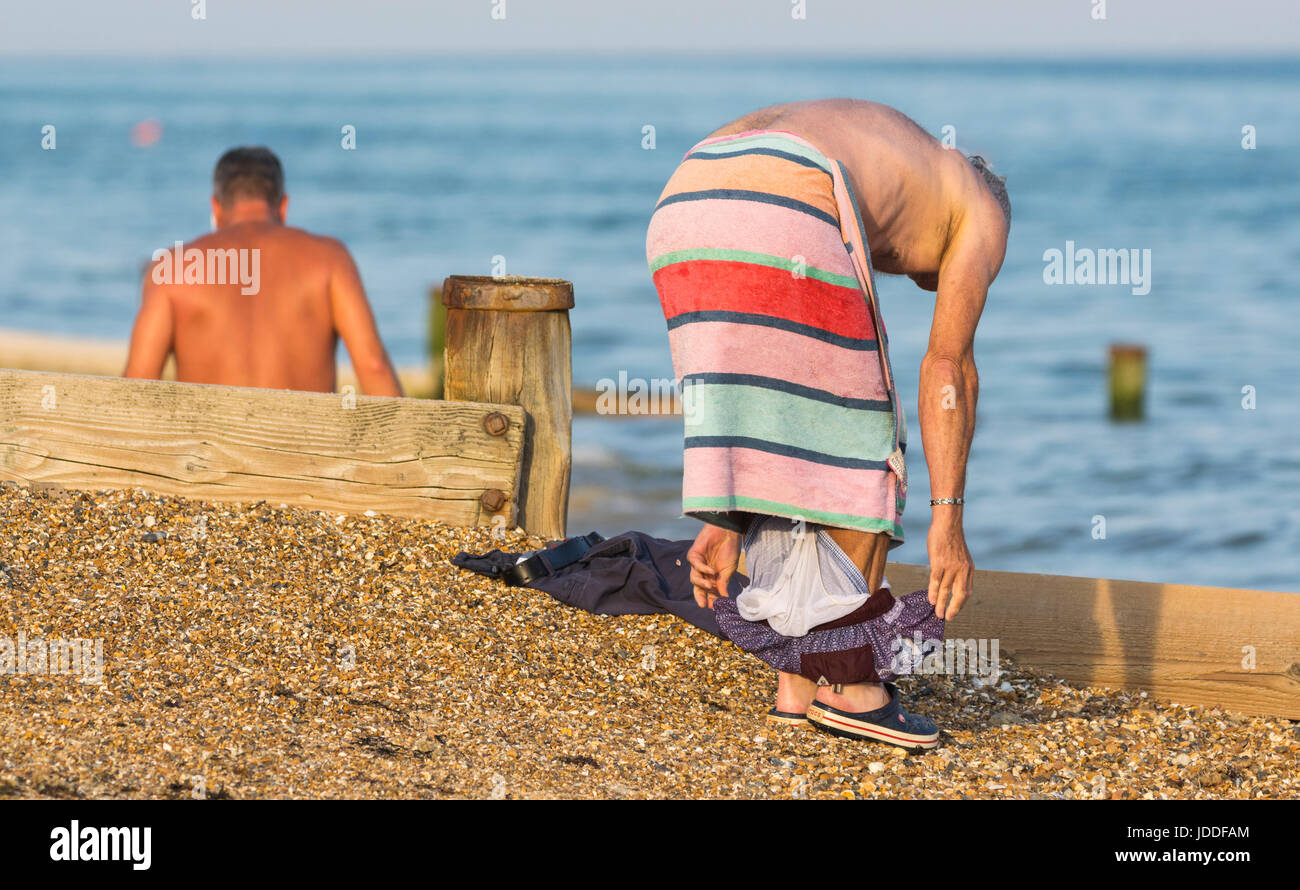 Man on the beach with a towel as he changes out of his swimming trunks. - Stock Image