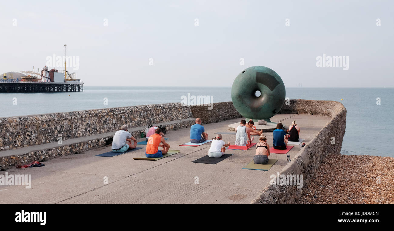 Brighton, UK. 20th June, 2017. A yoga class enjoys the continuing hot weather on Brighton seafront early this morning Stock Photo